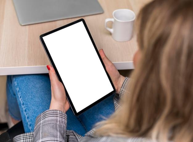 Mulher segurando um tablet em branco
