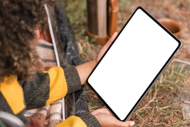 Mulher segurando um tablet enquanto acampa ao ar livre