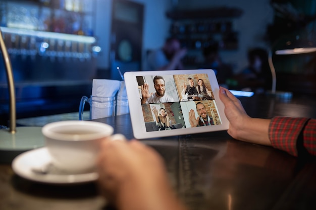 Mulher segurando um tablet para videochamada enquanto bebe café