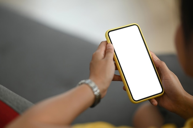 Mulher segurando um telefone celular com tela branca em branco.