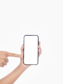 Mulher segurando um telefone celular com uma tela em branco na parede branca, close-up