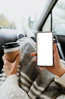 Mulher segurando um telefone em branco e uma xícara de café