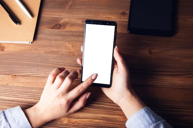Mulher segurando um telefone inteligente na mesa de trabalho