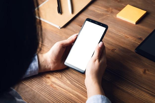 Mulher segurando um telefone inteligente no fundo da mesa de trabalho