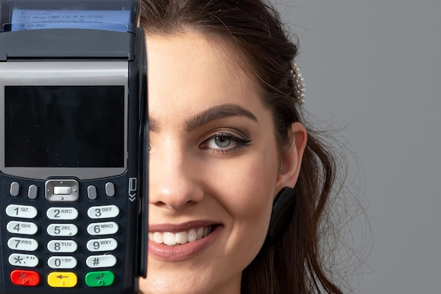 Mulher segurando um terminal de pagamento bancário moderno sem fio para processar e adquirir pagamentos com cartão de crédito