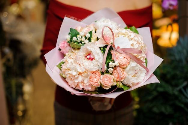 Mulher segurando um terno buquê de flores cor de rosa para o dia dos namorados