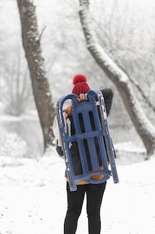 Mulher segurando um trenó ao ar livre