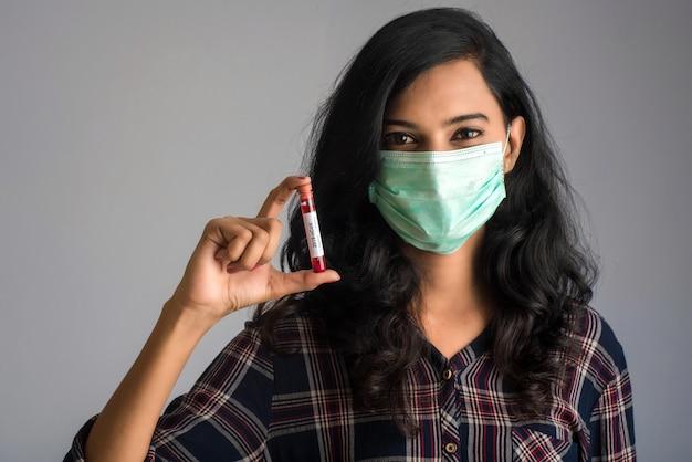 Mulher segurando um tubo de ensaio com amostra de sangue para análise de coronavírus ou 2019-ncov.