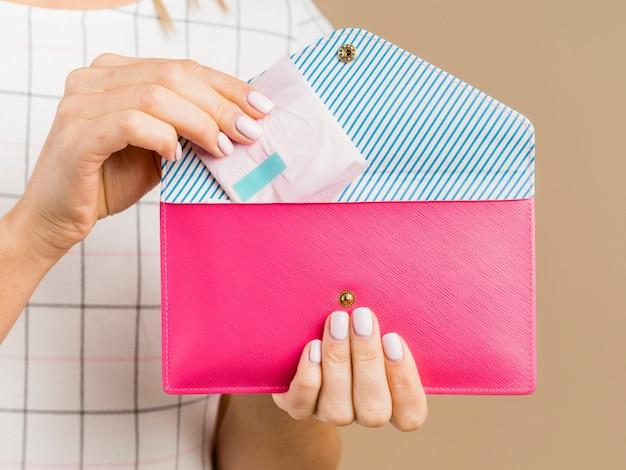 Mulher segurando uma almofada e uma carteira rosa