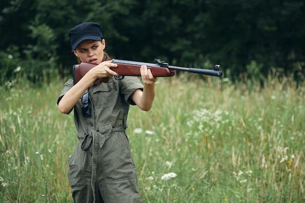 Mulher segurando uma arma com o objetivo de caça ao ar livre macacão verde vista recortada
