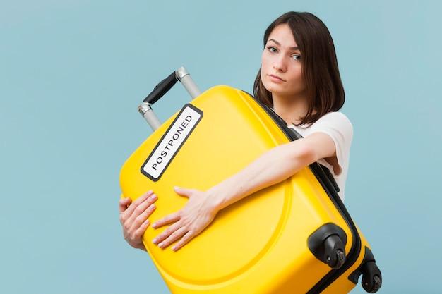 Mulher segurando uma bagagem amarela com um sinal adiado