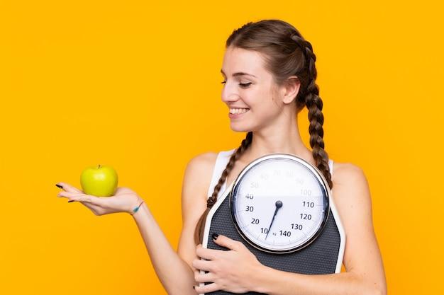 Mulher segurando uma balança sobre parede amarela