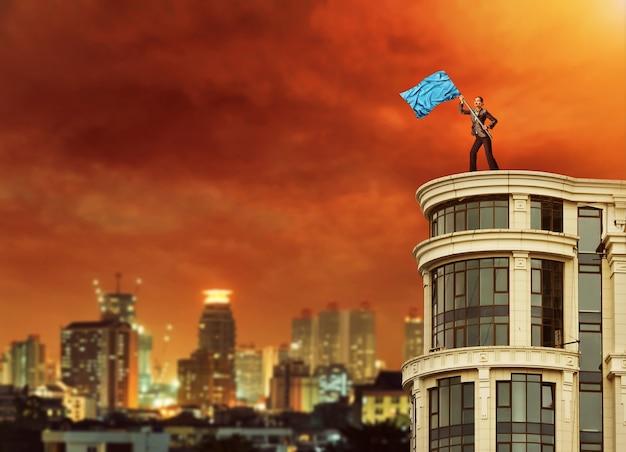 Mulher segurando uma bandeira azul em pé no topo de um prédio alto à noite