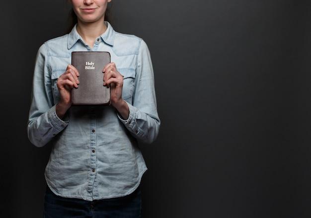 Mulher segurando uma bíblia nas mãos, usando roupas casuais sobre fundo cinza