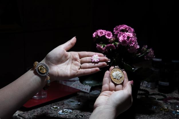 Mulher segurando uma bijuteria floral dourada