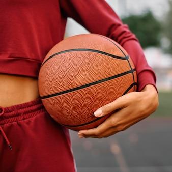 Mulher segurando uma bola de basquete, close-up ao ar livre