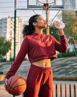 Mulher segurando uma bola de basquete e bebendo água