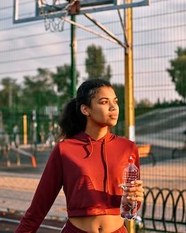 Mulher segurando uma bola de basquete e uma garrafa de água