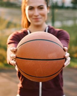 Mulher segurando uma bola de basquete na frente dela