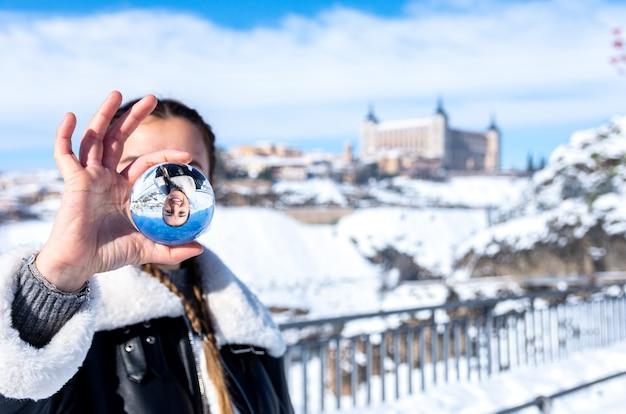 Mulher segurando uma bola de cristal na cidade nevada de toledo
