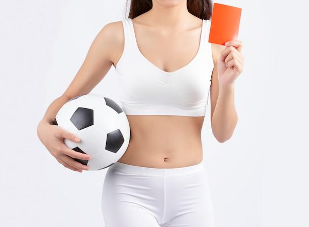 Mulher segurando uma bola de futebol com um cartão vermelho