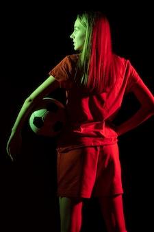 Mulher segurando uma bola de futebol de costas
