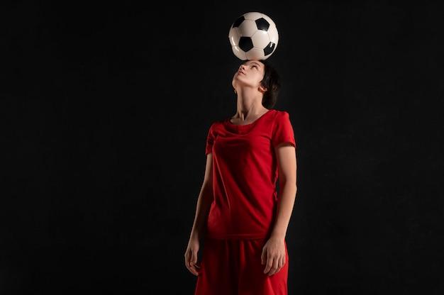 Mulher segurando uma bola de futebol na cabeça