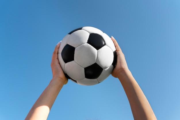 Mulher segurando uma bola de futebol no ar