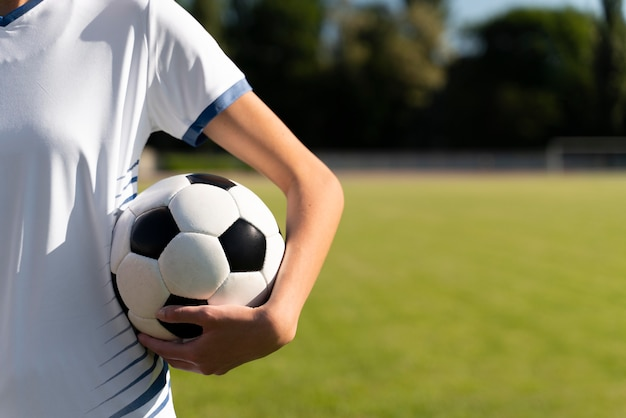 Mulher segurando uma bola de futebol no campo