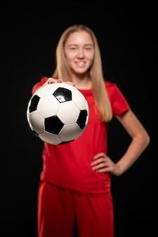 Mulher segurando uma bola de futebol
