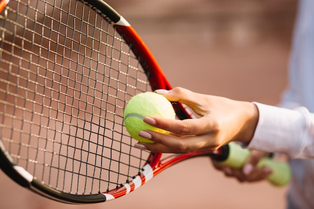 Mulher segurando uma bola de tênis e raquete
