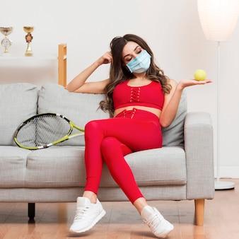 Mulher segurando uma bola de tênis enquanto usava uma máscara médica