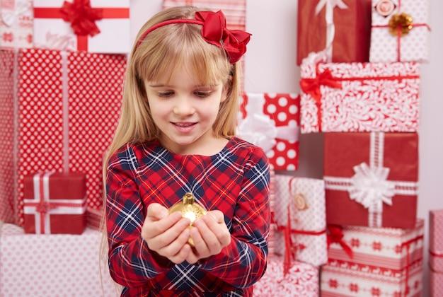 Mulher segurando uma bola dourada de natal