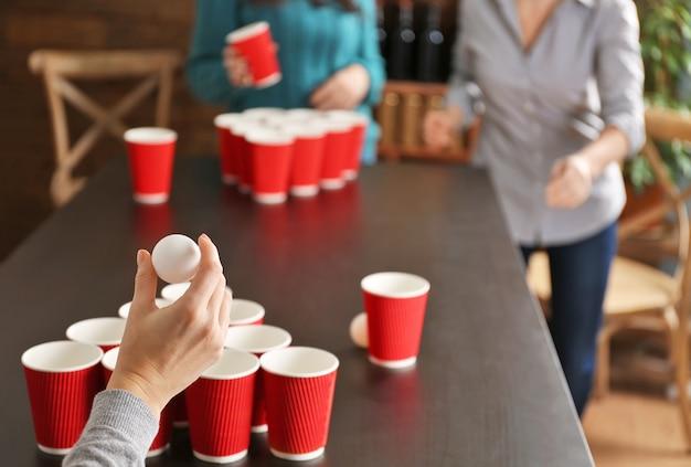 Mulher segurando uma bola para o jogo beer pong Foto Premium