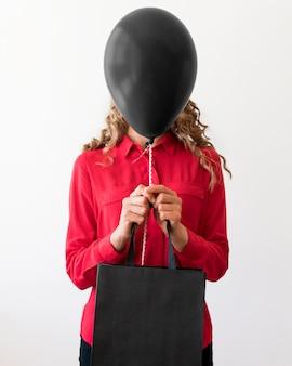 Mulher segurando uma bolsa e um balão preto cobrindo o rosto