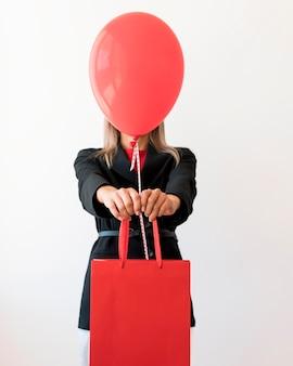 Mulher segurando uma bolsa e um balão vermelho cobrindo o rosto