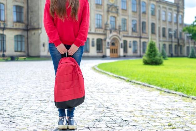 Mulher segurando uma bolsa vermelha do campus