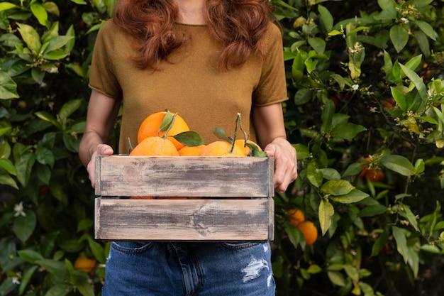 Mulher segurando uma caixa cheia de laranjas nas mãos