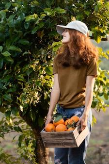 Mulher segurando uma caixa com laranjas