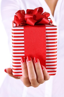 Mulher segurando uma caixa com um presente em um plano de fundo branco