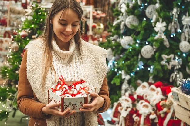 Mulher segurando uma caixa de brinquedo. bolas decorativas de natal