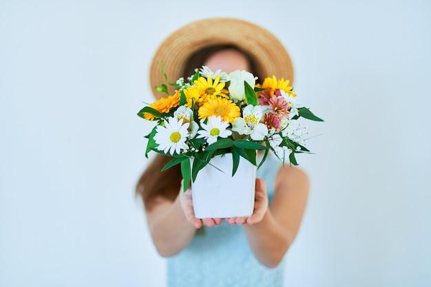 Mulher segurando uma caixa de chapéu decorativa colorida com flores frescas na primavera