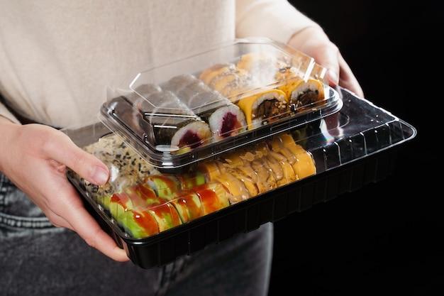 Mulher segurando uma caixa de conjunto de sushi em fundo preto