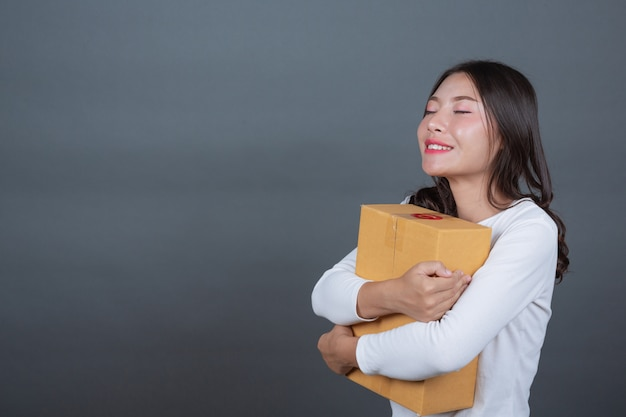 Mulher segurando uma caixa de correio marrom made gestos com linguagem gestual.