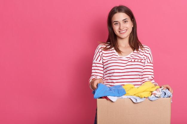 Mulher segurando uma caixa de doações cheia de roupas