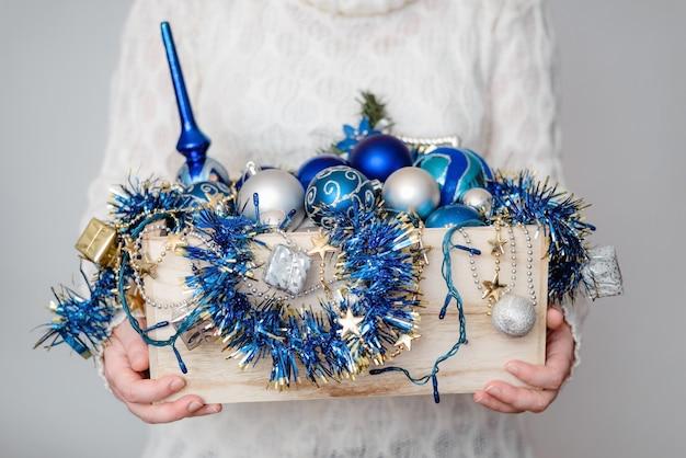 Mulher segurando uma caixa de madeira cheia de enfeites de decoração para árvores de natal plano de fundo de natal ou ano novo