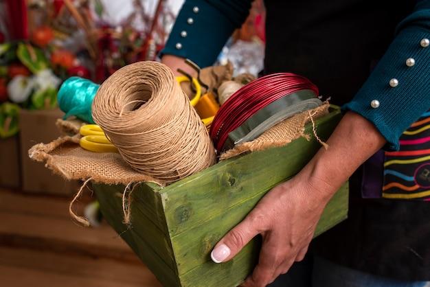 Mulher segurando uma caixa de madeira com ferramentas em uma floricultura