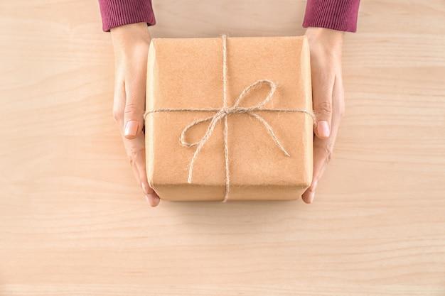 Mulher segurando uma caixa de presente de pacote em fundo de madeira