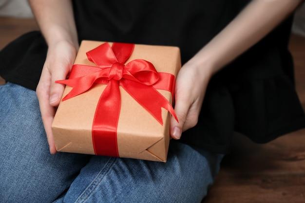 Mulher segurando uma caixa de presente dentro de casa