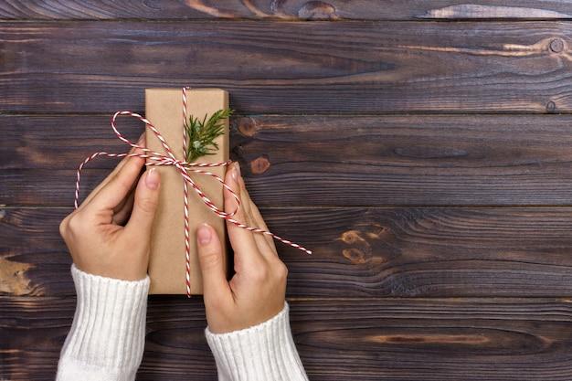Mulher segurando uma caixa de presente em um gesto de doação
